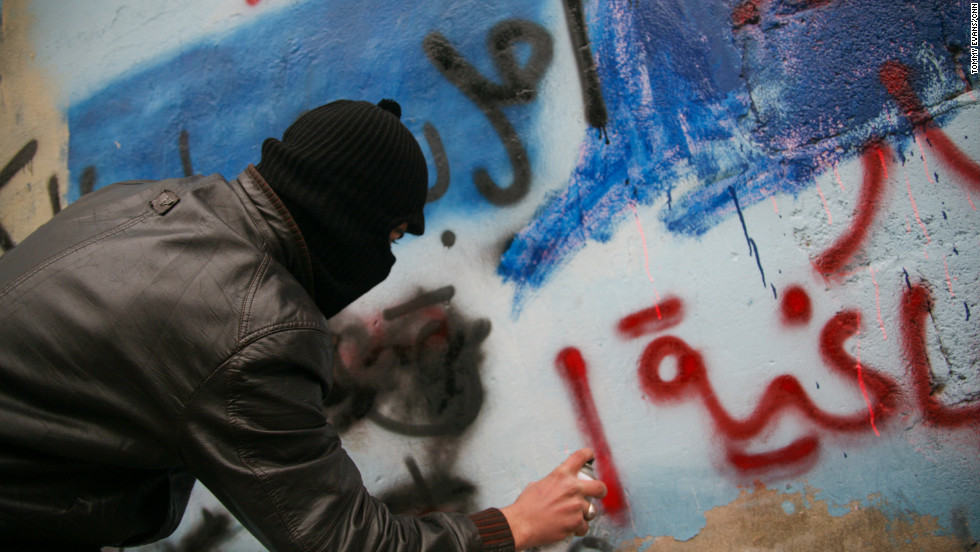 A protester spray paints anti-Assad graffiti.