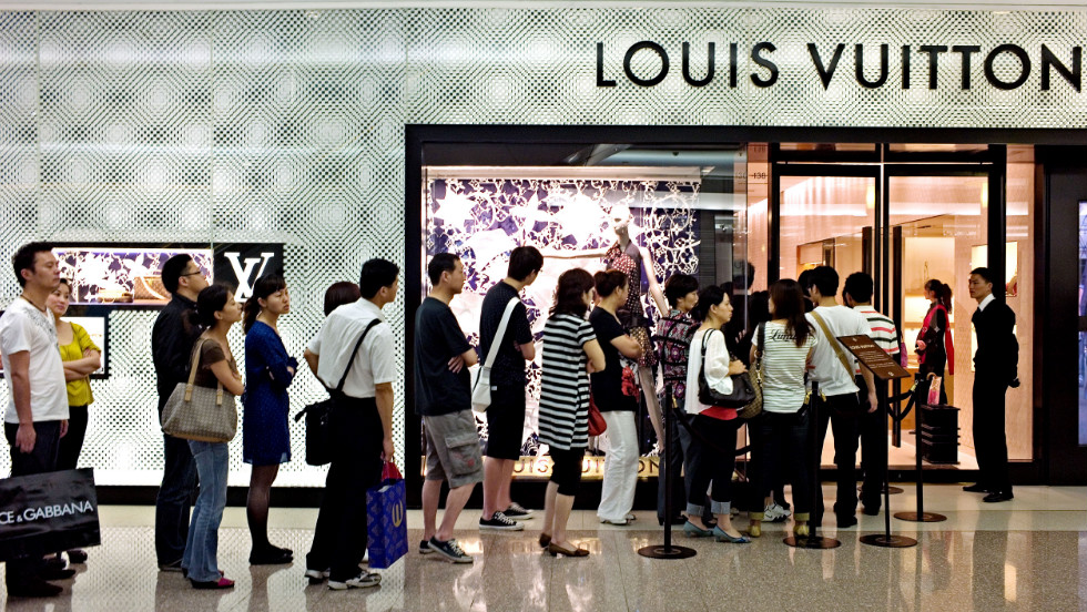 Shoppers queue to enter a shop of French luxury brand Louis Vuitton in a shopping mall in Shanghai.