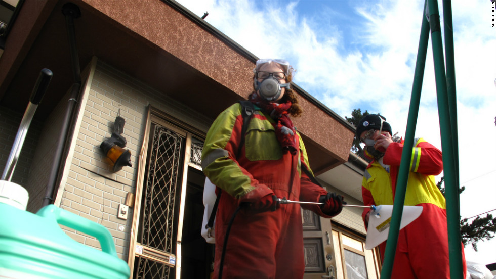 Two volunteers preparing to go in and bleach and scrub the wooden frames of a house.