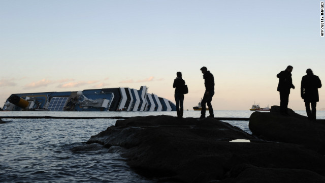 People take pictures in front of the cruise liner Costa Concordia lying aground on January 20, 2012 in front of the harbour of the Isola del Giglio (Giglio island) after hitting underwater rocks on January 13.