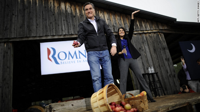 Republican presidential hopeful Mitt Romney tosses apples to supporters as he holds a campaign rally at Harmon's Tree Farm in Gilbert, South Carolina, January 20, 2012.