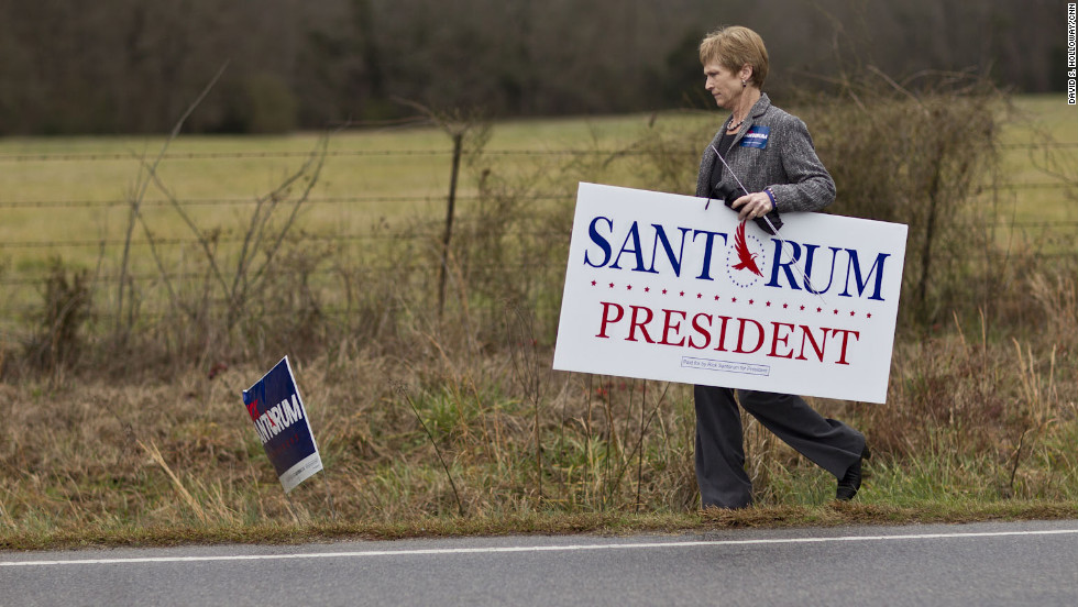 Trish Mozdzierz, volunteer field director for Rick Santorum's campaign in Lexington County, places campaign signs along Amicks Ferry Road near Chapin, South Carolina.