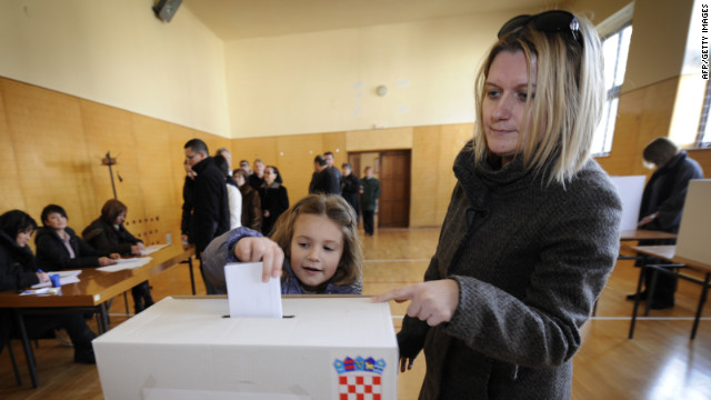 A Croatian girl casts her mother's ballot Sunday during the country's bid to join the European Union.