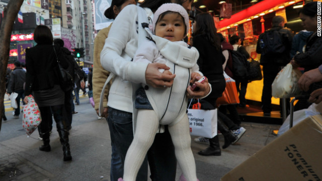 In a photo taken on January 18, 2012, a baby is carried by her mother in Hong Kong.