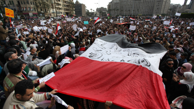 Protestors carry a large Egyptian flag through Tahrir Square on January 31, 2011 in Cairo, Egypt.