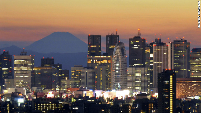 Japan's highest mountain, Mount Fuji, rises behind Tokyo's skyscraper skyline, as the sun sets in this photo last year.