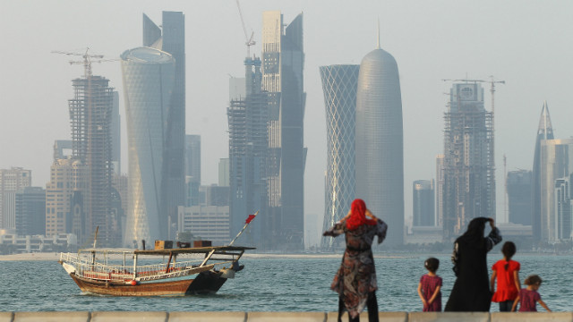 A traditional Arab ship in Doha's harbor with the Qatari capital's futuristic skyline in the background.