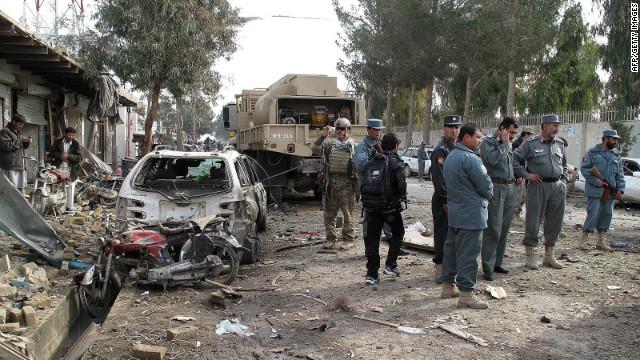 Afghan policemen investigate the scene of the attack in Lashkar Gah on Thursday.