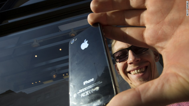 A man takes a photograph using his iphone 4S at an Apple store in London in October.