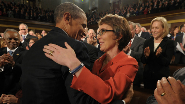 U.S. President Barack Obama embraces U.S. Rep. Gabrielle Giffords as members of Congress applaud before his State of the Union address.