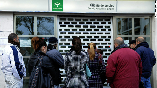 People wait in line in front of a government employment office in Sevilla, Spain, in early 2012.