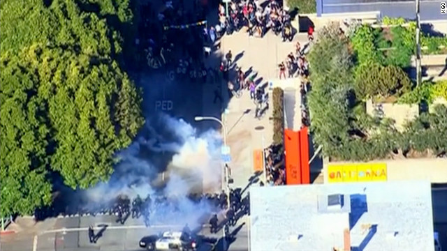 Smoke rises between Occupy Oakland protesters and police cordoning off an intersection Saturday.