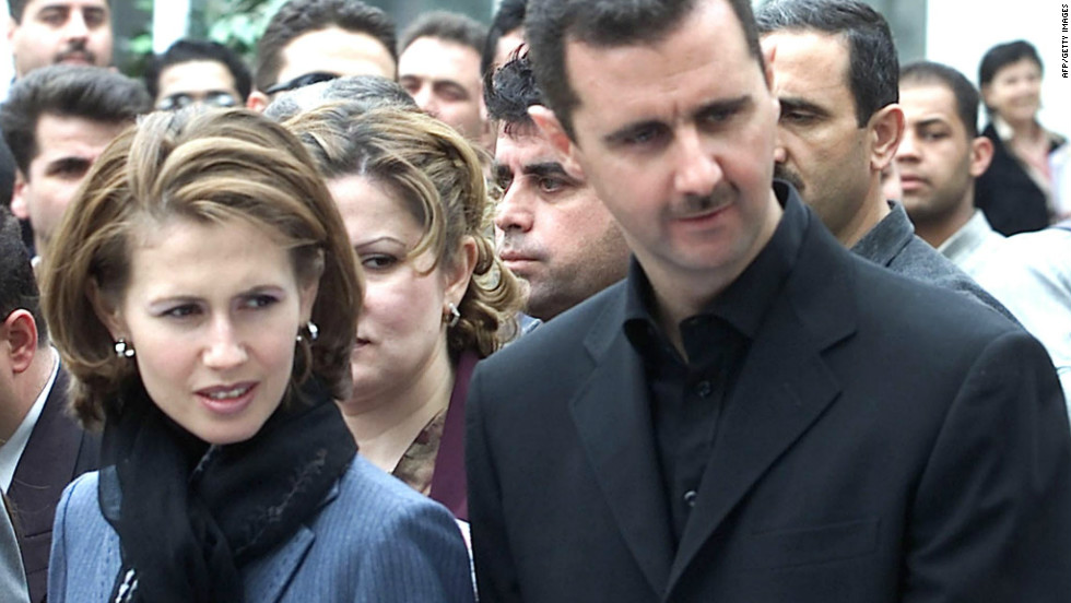 Syrian President Bashar al-Assad walks with his wife Asma through the Sham Fair in Damascus on April 26, 2002.