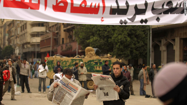 "Egyptian anti-government protesters read newspapers under a banner reading ""People want the regime to fall"" at Tahrir Square in 2011. But not all elements of Egyptian society are anti-Mubarak."