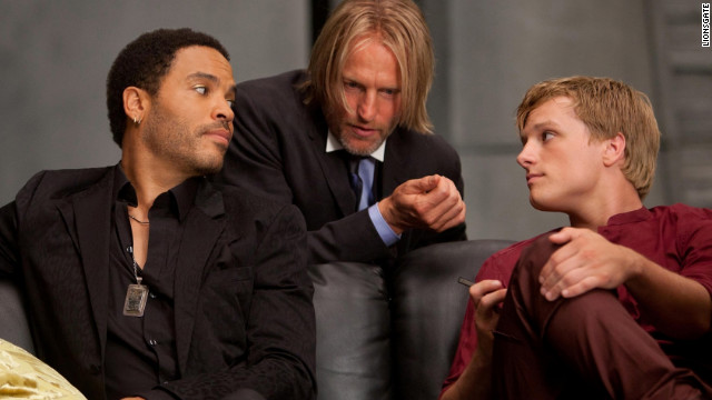 "Lenny Kravitz, left, stars in ""The Hunger Games"" as Cinna, with Woody Harrelson as Haymitch and Josh Hutcherson as Peeta."