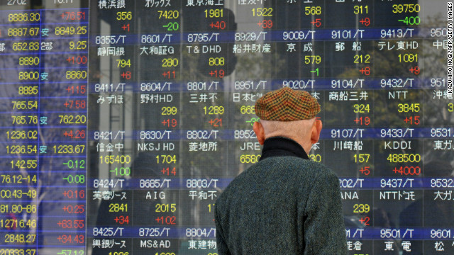 A man looks at an electronic board displaying the Nikkei 225 index at the Tokyo Stock Exchange in Tokyo on February 2.