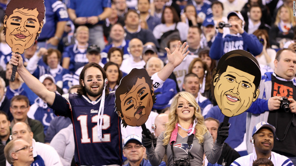 Patriots supporters hold up giant masks of quarterback Tom Brady (left) and tight end Arron Hernandez as the players conduct their press conferences.