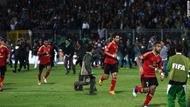Players run for safety as fans riot during the Egyptian Premier League match between al-Ahly and al-Masry.