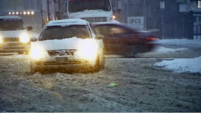 Cars travel through snow-covered streets in Denver on Friday.