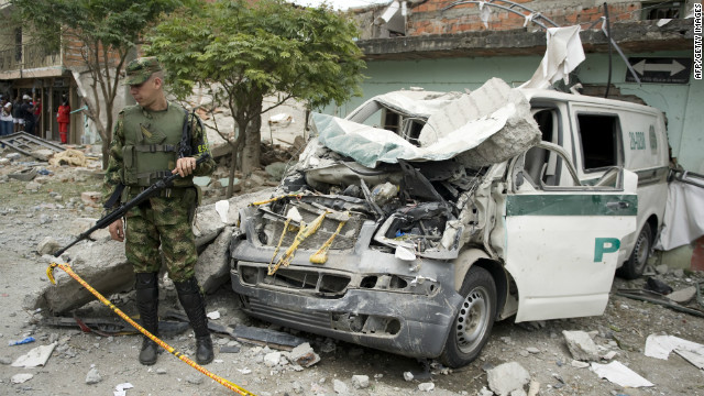 A police officer stands beside a police vehicle destroyed in an attack with a cylinder bomb