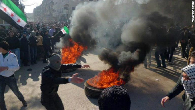 Syrian protesters burn tires and wave independence flags during an anti-regime demonstration in the Damascus suburb city of Daraya on February 4, 2012.