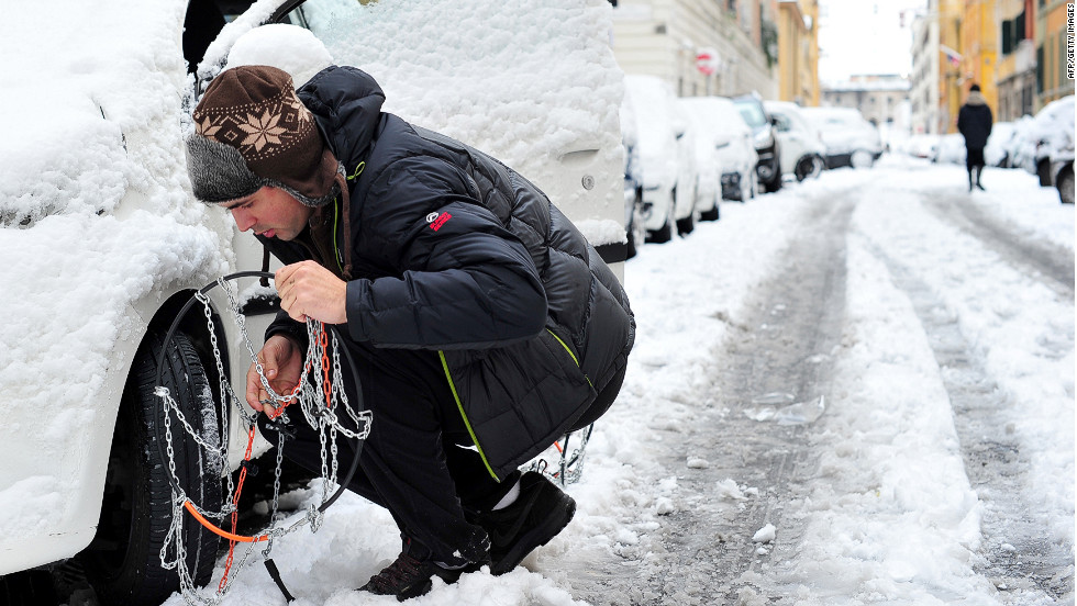 A man puts snowchains on his car Saturday in Rome. Heavy snowfall caused the Italian capital to grind to a halt.