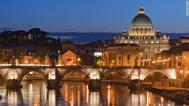 A view of Rome: The River Tiber, where you can see the iconic dome of the Basilica di San Pietro towering over the Vatican City.