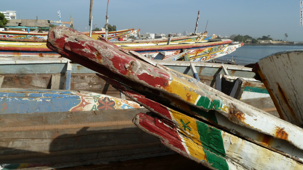 Aged wooden boats parking along the beaches of Dakar, weathered by time.