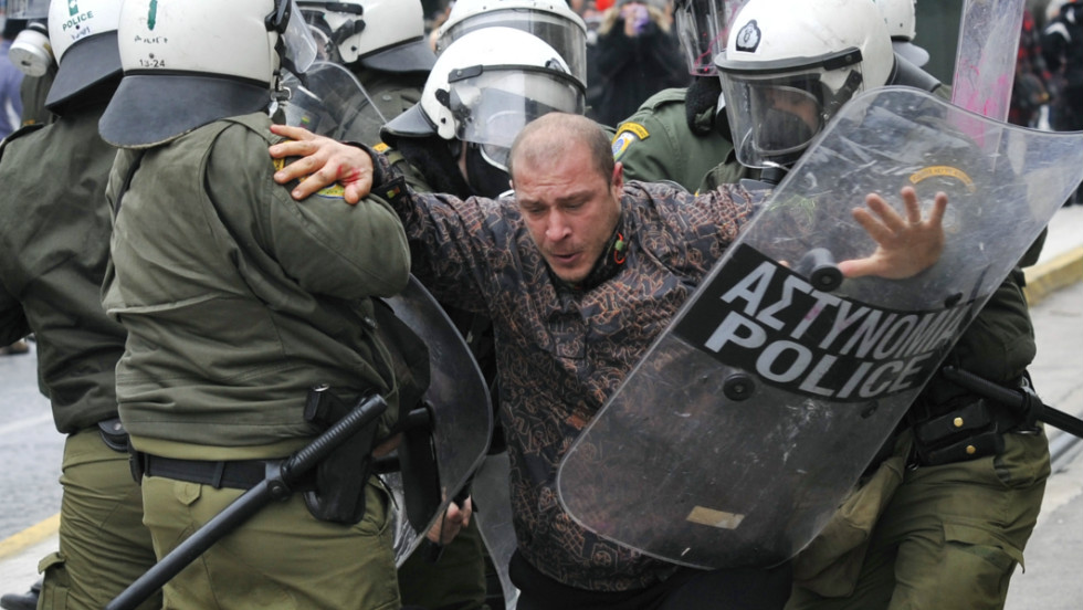 Riot police detain a protester during a 48-hour general strike in Athens on February 10, 2012 in response to new austerity cuts. Greece needs the euro zone ministers to sign off on a new €130 billion ($172.6 billion) bailout deal.