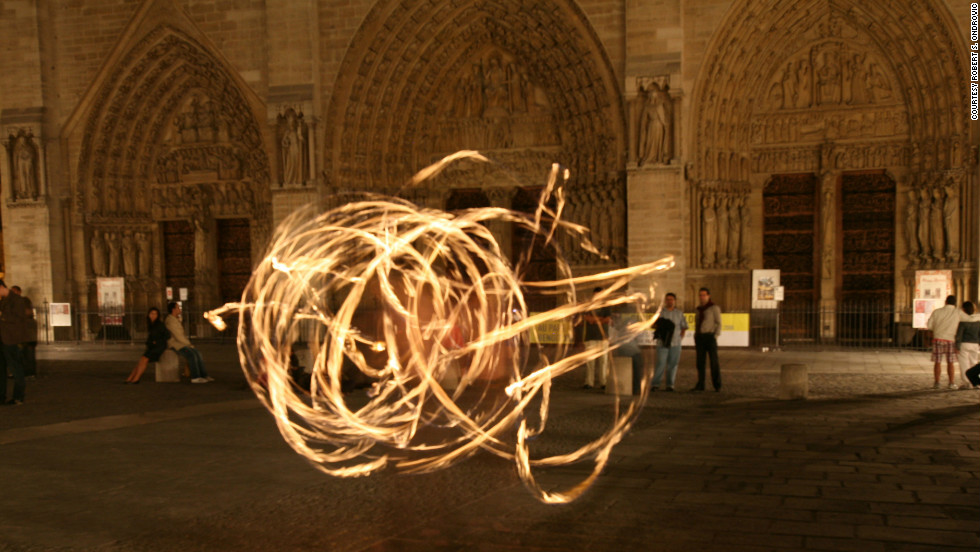 "Robert S. Ondrovic shot this photo of ""a street performer outside of Notre Dame who was juggling batons that were on fire on a beautiful summer evening at midnight."" The long exposure caused the juggler to appear transparent."