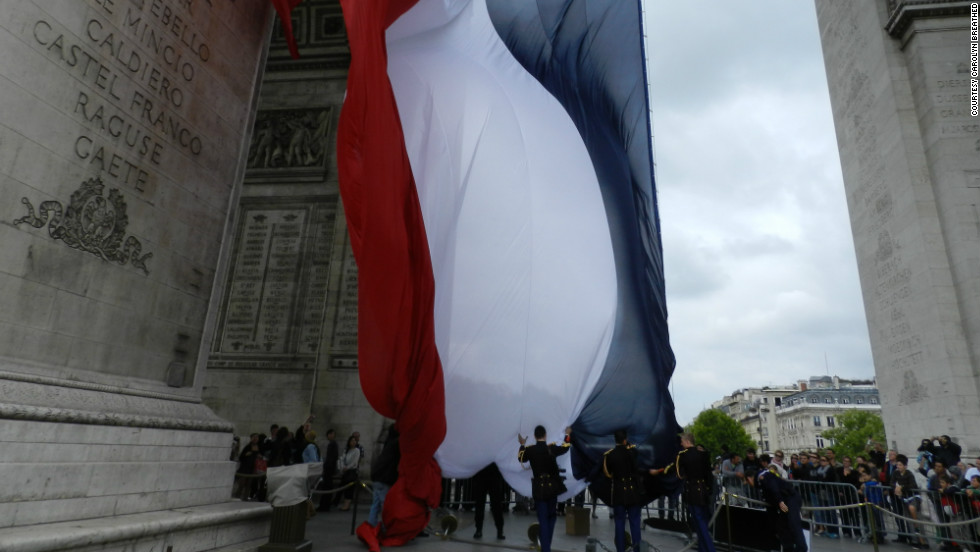 "Carolyn Breathed snapped this shot of the French military raising the flag the day before Bastille Day. ""It was really thrilling to finally see the French flag flying proudly under the Arc de Triomphe."""