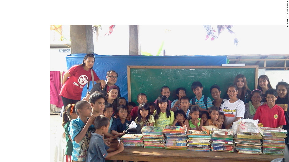 "Avena and other Operation VALENTINES volunteers  pose with local children near their newly donated collection. ""Though we left about half a ton of clothes, we decided to pack books; books enough to start a small library for elementary school children,"" Avena said."