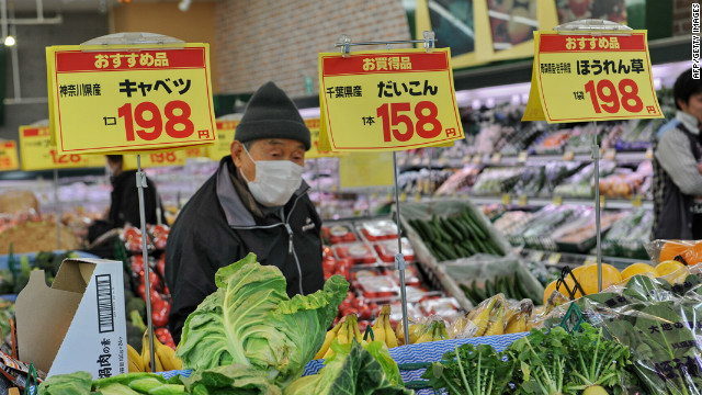 A woman walks past vegetables in a supermarket in Nihonmatsu, Fukushima prefecture, on March 26, 2011.