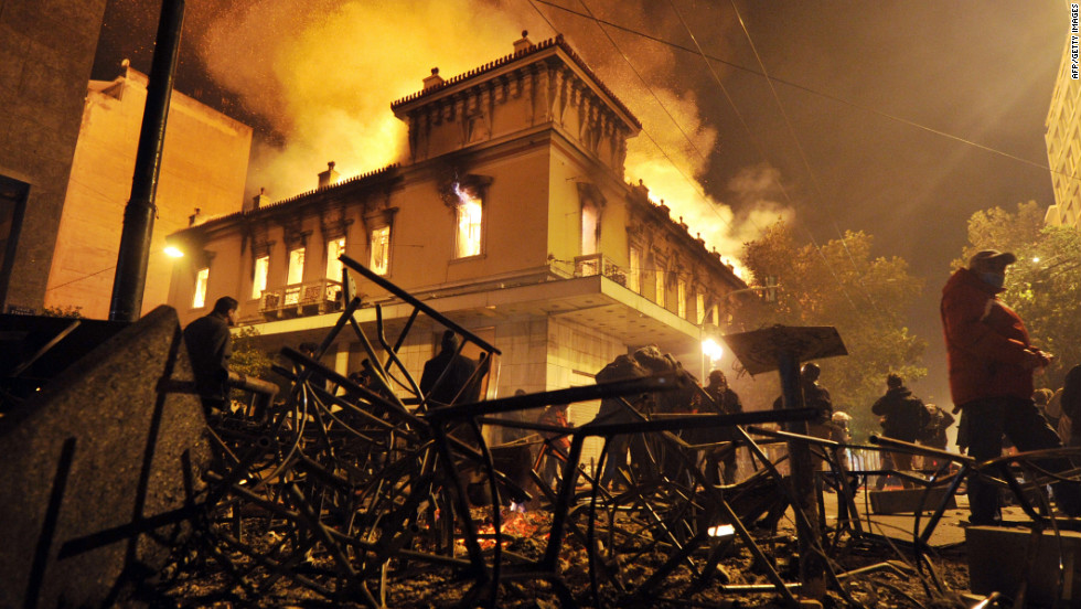 A fire engulfs a store during clashes between protesters and riot police near the Greek parliament in Athens