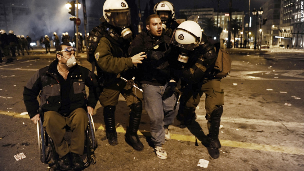 A protester is arrested and taken away by riot police while a man in a wheelchair watches.