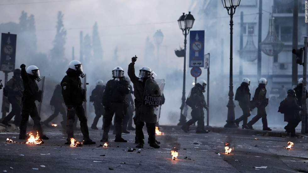 Tear gas and smoke create an eerie, fog-like atmosphere as masked riot police stand guard.