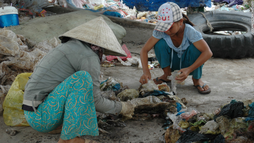 A  girl and her mother scrounge through garbage in Rach Gia, Vietnam. Some 200 families - three generations of Cambodians - live on two dumps there.
