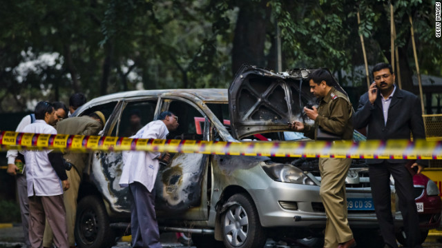 Police and forensic officers examine a damaged Israeli embassy vehicle after an explosion on February 13, 2012 in New Delhi, India