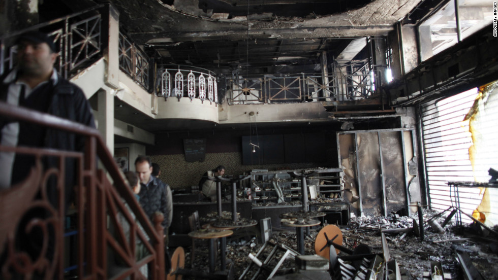 People stand in a damaged building after it burned in central Athens on February 13, 2012.