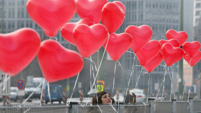 A woman fixes red heart-shaped balloons on a fence on Februray 14, 2012 in Berlin. Every year on February 14, or Valentine's Day, lovers across the World offer flowers or other presents to eachother to express their feelings.