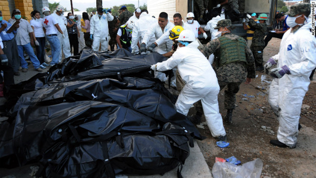 Honduran forensic workers and soldiers remove corpses in plastic bags from the National Prison in Comayagua on Wednesday.