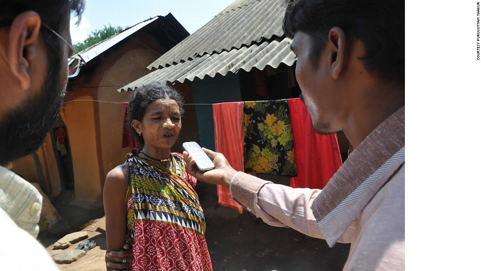 A tribal woman is interviewed by a citizen journalist.