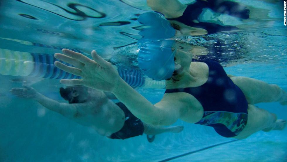 Team members Jeff Dauler and Nancy Klinger do a swim workout with coach April Burkey