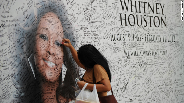 A Fillipino fan of US pop diva, Whitney Houston, signs a tribute mural displaying a portrait of her idol at a mall in Manila on February 17, 2012. Houston, who died on February 11 aged 48 in a Beverly Hills hotel, will be laid to rest on February 18, after a private funeral service at the New Jersey Baptist church where she grew up singing in a gospel choir. AFP PHOTO / TED ALJIBE (Photo credit should read TED ALJIBE/AFP/Getty Images)