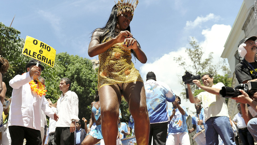 A  Beija Flor samba school dancer performs during the launch of carnival in Rio de Janeiro on Friday. Neighborhoods across the city host block parties that attract revelers by the thousands -- and sometimes more than a million. They drink and dance behind samba bands that wind their way through the streets.