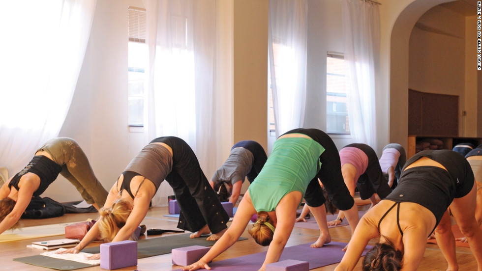 Participants in an afternoon yoga class at Kripalu practice downward facing dog.