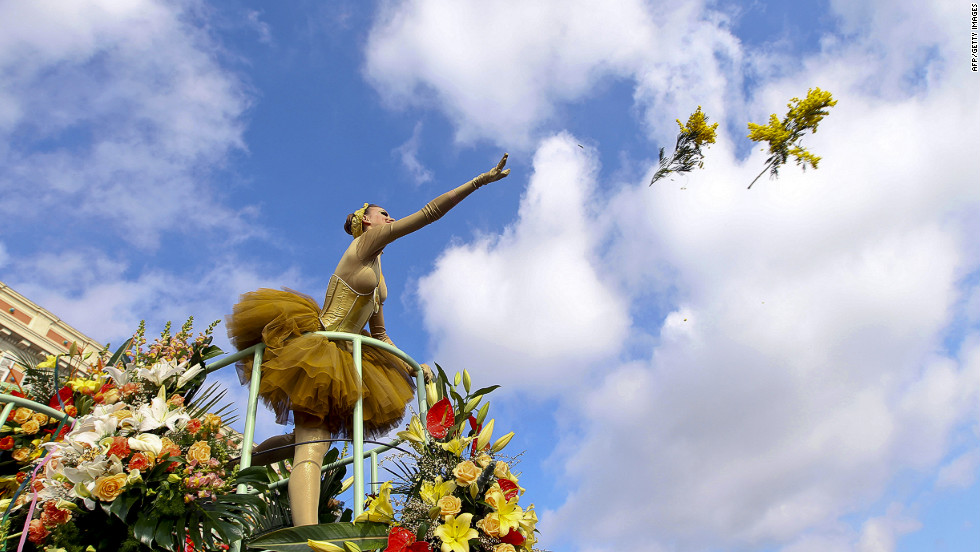 A woman throws flowers as she takes part in a carnival parade in Nice, France, on Saturday.