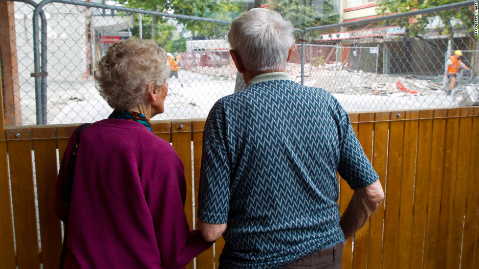 An elderly couple watch the demolitional of buildings they grew up around in downtown Christchurch on February 21, 2012.