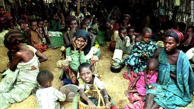 BAIDOHA, SOMALIA - AUGUST 6: Women and children sit inside a shelter 06 August 1992 at a feeding center run by the International Committee for the Red Cross (ICRC) in Baidoha, Somalia. The shelter was established to feed a few thousand of the 30,000 refugees suffering from famine, severe drought and the effects of 18 months of civil war. (ALEXANDER JOE/AFP/Getty Images)