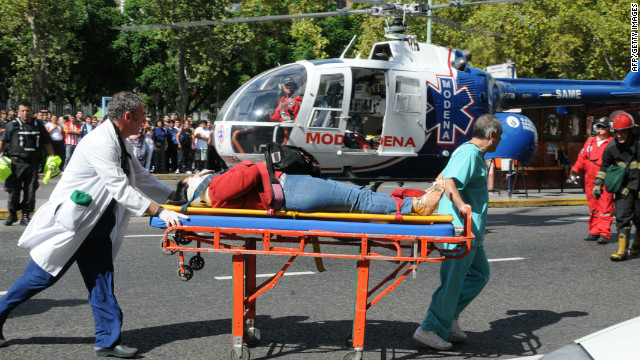 An injured woman is transported in a stretcher next to a helicopter after a train crashed in Buenos Aires on February 22, 2012.